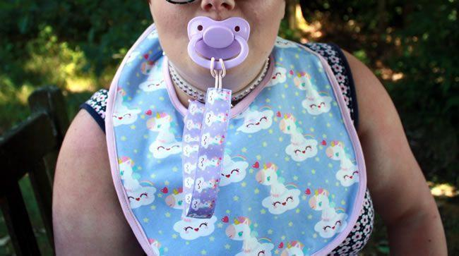 Image showing Little Rae wearing a Bib, pacifier and retainer in public