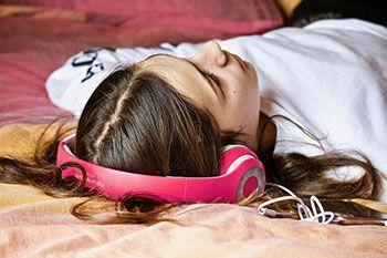 Woman laying on the bed listening through headphones