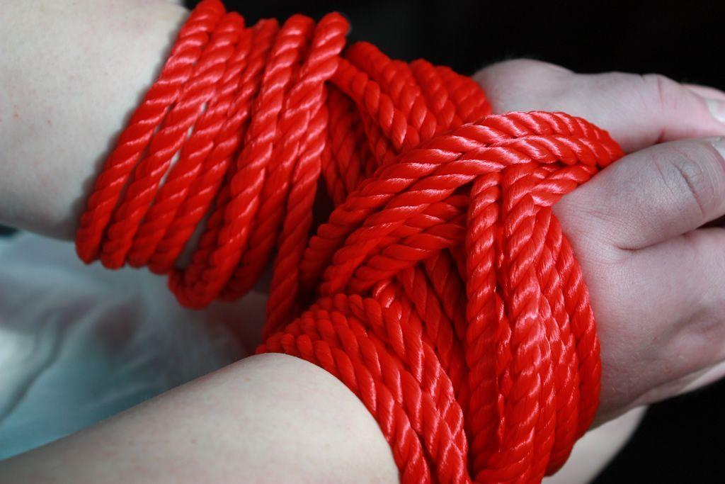 This weeks pic shows some red rope restrasining a submissive.