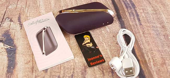 Obrázek znázorňující Satisfyer Pro Traveler, jeho nabíjecí kabel a pokyny